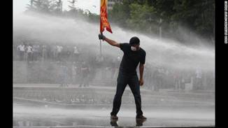 A protester faces water cannons during a clash with police at an anti-government demonstration in Ankara on June 16.